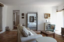 Pale sofa and armchair around coffee table in living room with terracotta floor tiles