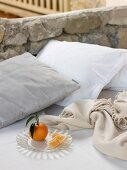 Orange on plate, cushions and blanket on bed against low stone wall