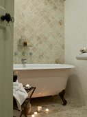 Tealights on stone-tiled floor next to free-standing clawfoot bathtub