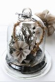 Christmas arrangement of fabric flowers and moss under glass cover