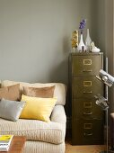 Comfortable sofa, retro filing cabinet and chrome standard lamp