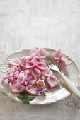 Hand-made pink felt bows, pink flowers and fork on white plate