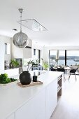 White island counter and spherical lamp in open-plan living area with view of countryside
