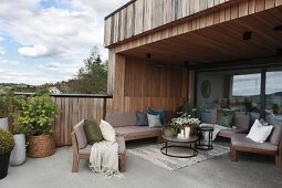 Roofed terrace with concrete floor adjoining wood-clad house