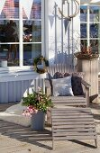 Lounger with cushions next to wintry flower arrangement on wooden terrace