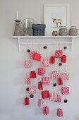 Advent calendar made from paper bags and fir cones hung from wall-mounted shelf