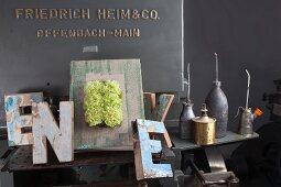 Einband mit grünen Nelken dekoriert, umgeben von Vintage Buchstaben und Ölflaschen
