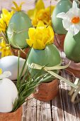 Green painted Easter eggs used as vases for yellow and white narcissus