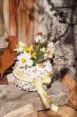 Narcissus and forsythia in vase covered in pieces of egg shell