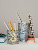 Writing utensils in metal tins decorated with coloured tangram triangles