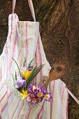 Aufgehängte Kochschürze mit Blumendekoration und Kochlöffeln