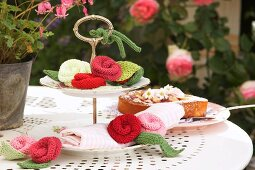 Cake stand decorated with various knitted flowers on white metal table