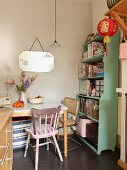Table and two chairs next to pale green, wooden, open shelving in corner of kitchen