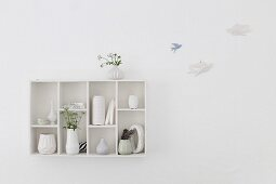 Collection of vases in wall-mounted display case next to bird ornaments mounted on wall