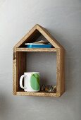 Books, cup and glasses on hand-made, wooden, house-shaped shelf