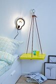 DIY shelf hung on wall from ropes and used as bedside table next to sconce lamp
