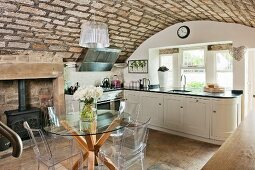 Rustic vaulted ceiling, designer furniture and traditional log burner in elegant country-house kitchen
