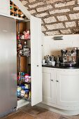 Fitted pull-out shelving and wine rack under vaulted stone ceiling in corner of kitchen