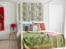 Four-poster bed with white-painted wooden frame, colourful patterned bedspread and retro-style scatter cushions