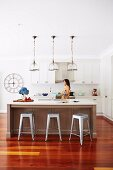 Kitchen island and retro bar stool under pendant lights, woman in front of white kitchen counter in background