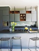 Elegant blue and grey fitted kitchen with counter and bar stools