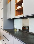 Elegant blue and grey fitted kitchen with serving hatch made from sliding glass panels
