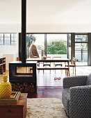 View through cosy living area with wood-burning stove to dining area and open terrace doors