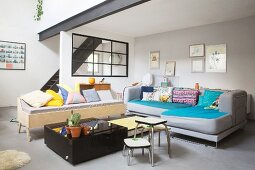 Colourful scatter cushions on sofa and black stairs leading to mezzanine