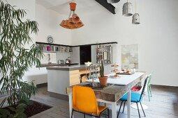 Offene Küche mit Küchentheke und Essplatz mit rustikalem Holzbohlentisch