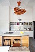 Reduzierte, weisse Einbauküche und Küchentheke mit naturbelassener Holzfront