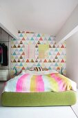 Colourful wallpaper on accent wall and green upholstered double bed frame in bright bedroom