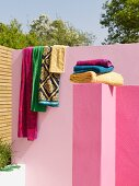 Towels stacked on pink wall in front of patterned towels draped over pink limewashed garden wall