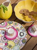 Cup and saucer on patterned plat, yellow salad bowl and lemon-shaped jug on wooden deck