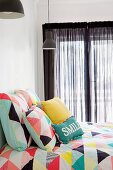 Colorful, geometrically patterned bed linen with matching pillows in front of windows with black curtains