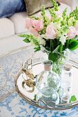 Romantic, pink bouquet of roses on a silver tray with a glass carafe