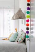 Colorful pompom garland on room door in bright bedroom with pendant lights and pastel-colored pillows
