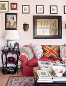 Red sofa, antique side table and gallery of pictures in living area