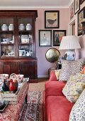 Gallery of pictures and antique display cabinet in eclectic living room