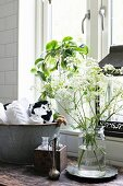 Rolled towels in vintage zinc tub next to glass bottles in wooden box and vase of cow parsley