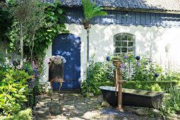 Vintage arrangement of pump and zinc bathtub in garden outside country house