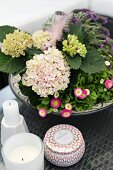 Bowl planted with hydrangea and daisies next to white candles and decorative pot