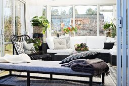 Cushioned bench in front of comfortable couch with white cushions and houseplants in conservatory extension