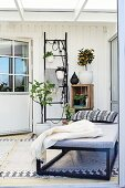 Couch, potted plants hung from black ladder frame in conservatory extension with Scandinavian ambiance