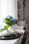 Blue hydrangea and structured vases on black tray