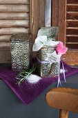 Rosemary bath salts in decorative tins and pink cyclamen on purple towel