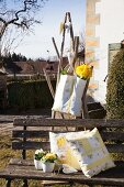 Daffodils in hand-made shopping bag above cushions on vintage garden bench