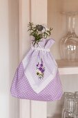 Small bag decorated with embroidered handkerchief hung from dresser door