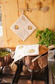 Hand-made potholders with patterns of stripes and roses in rustic kitchen