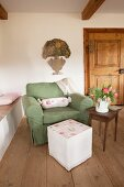 Romantic pattern of roses on hand-sewn, loose pouffe cover and bolster on armchair