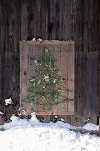 Weihnachtliche DIY-Vogelfutterstation als Baummotiv mit aufgespannten, grünen Schnüren auf rustikaler Holzunterlage